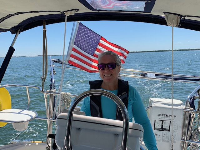 Student Sailor behind wheel of boat