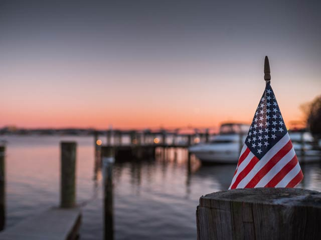 American Flag in Focus, Dock and Bay in Background